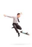 Businessman performing tricks with skateboard Stock Photos