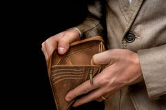 Businessman person holding an empty wallet isolated on black Royalty Free Stock Images