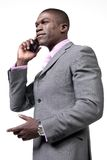 Businessman on the phone. Black Business man on the cell phone and smiling. White background Royalty Free Stock Images