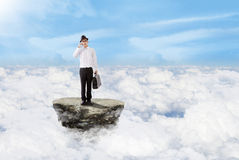 Businessman on the phone above clouds Stock Image