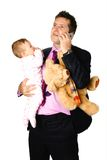 Businessman on phone with baby. Young businessman father holding his baby and teddy under one arm while making phone call, concept of family life and work stock photo
