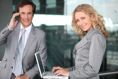 Businessman on phone and businesswoman with laptop Stock Photos