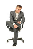 Businessman with phone on chair Stock Images