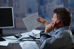 Businessman on phone checking document Stock Photos