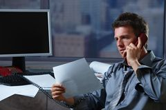 Businessman on phone checking document Stock Photography
