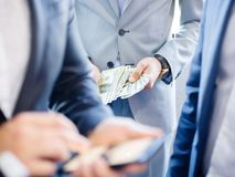 Businessman with a phone close-up on other businessmen with phones. Businessman with phone on other businessmen in good expensive suits with phones and money of stock image