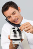 Businessman on phone and consulting a card holder Royalty Free Stock Images