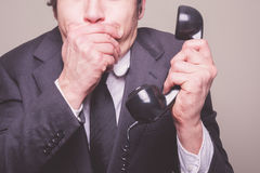 Businessman on phone covering his mouth Stock Photo
