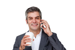 Businessman on phone while drinking a coffee Royalty Free Stock Image