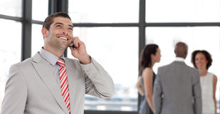 Businessman on the phone in front of business team Stock Photos
