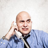 Businessman on the phone. Frustrated businessman in messy situation talking on the phone Stock Photography