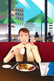 Businessman on the phone while having breakfast in a cafe Royalty Free Stock Photography