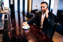 Businessman on the phone having a coffee. At the counter in a bar Royalty Free Stock Images