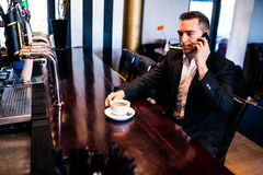 Businessman on the phone having a coffee. At the counter in a bar Royalty Free Stock Photography