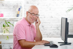 A businessman at phone in his office Stock Photography