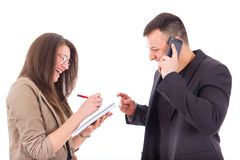 Businessman on the phone and his secretary writing down notes. Smiling businessman on the phone and his secretary writing down notes Stock Photo