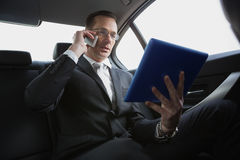 Businessman on the phone holding tablet pc. In his car royalty free stock image