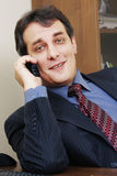 Businessman with phone inclining right Stock Photography