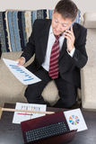 Businessman with phone at laptop Royalty Free Stock Image