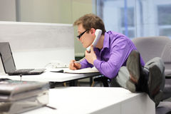 Businessman on phone looking at screen - bad sitting posture Stock Photo