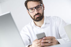Businessman with a phone is looking at you Stock Photography