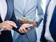 Businessman with a phone close-up on other businessmen with phones. Businessman with phone on other businessmen in good expensive suits with phones and money of royalty free stock images