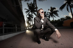 Businessman on the phone outside. Young businessman squatting and talking on the phone outside Stock Photos