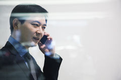 Businessman on the phone in parking garage, looking through window Stock Image