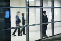 Businessman on the phone in parking garage, looking through window Stock Photos