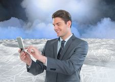 Businessman on phone in sea of documents under sky clouds. Digital composite of Businessman on phone in sea of documents under sky clouds stock photo