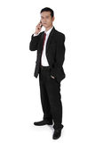 Businessman on phone, standing and looking to camera Stock Photo