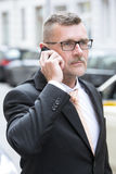 Businessman with phone in the street Stock Image