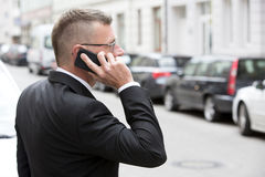 Businessman with phone in the street Stock Photos