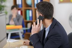 Businessman on phone while talking to worker. Businessman on the phone while talking to worker Stock Image