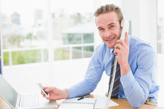 Businessman on the phone while text messaging Royalty Free Stock Image