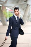 Businessman on phone and traveling with bag Stock Photography