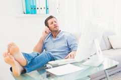 Businessman on the phone using his computer with his feet up Royalty Free Stock Photo