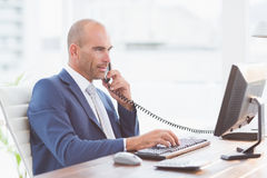 Businessman on the phone and using his computer Royalty Free Stock Image