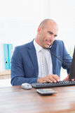 Businessman on the phone and using his computer Royalty Free Stock Images
