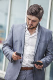 Businessman with phone and wallet in the urban district Stock Photography