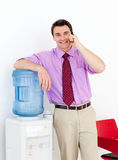 Businessman on phone by the watercooler Royalty Free Stock Image