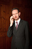 Businessman on Phone with Wood Panels Stock Images