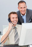 Businessman on phone and working with a colleague Stock Images