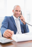 Businessman on the phone and writing notes. In his office Royalty Free Stock Photography