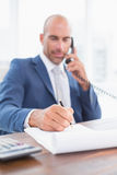 Businessman on the phone and writing notes. In his office Royalty Free Stock Photos