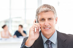 Businessman phoning while his team is working Stock Photography