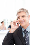 Businessman phoning while his team is working Royalty Free Stock Image