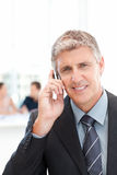Businessman phoning while his team is working Stock Photo