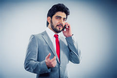 Businessman phoning with smartphone. Grey background Stock Photo