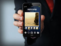 Businessman with photo editor smartphone Stock Photos
